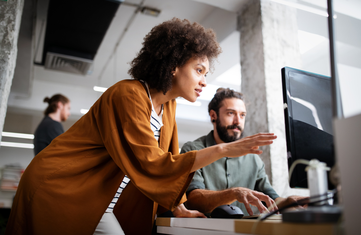 woman-discussing-account-based-marketing-with-man-at-desk-with-computer-monitor-in-office