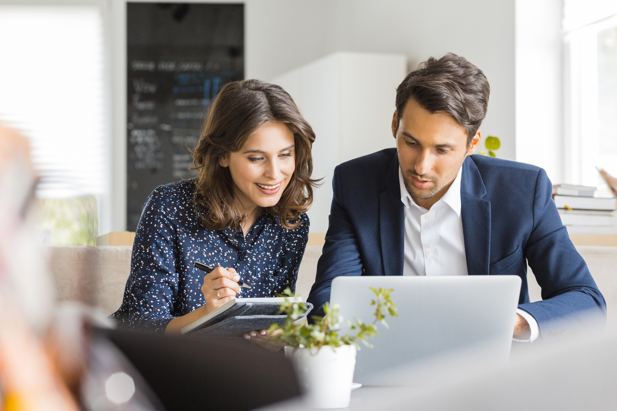 man-and-woman-sitting-at-table-while-working-on-laptop-together