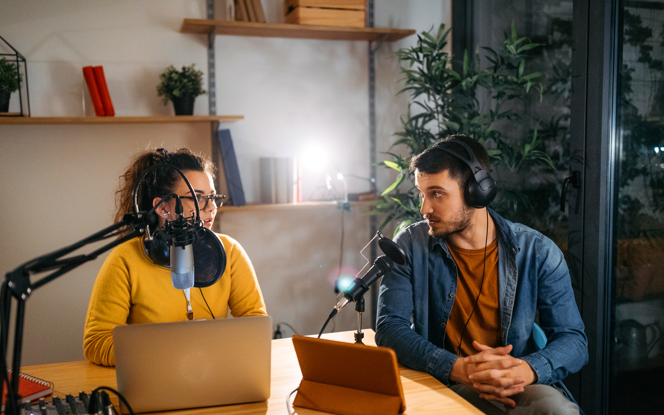 woman-and-man-seated-at-table-with-microphones-and-laptop-recording-podcast