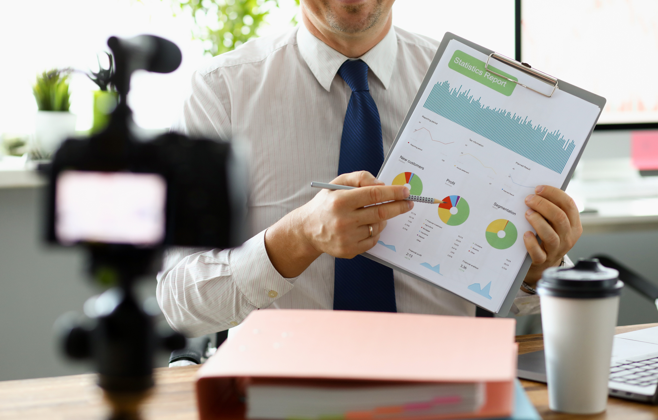businessman-filming-b2b-fintech-video-explaining-data-on-clipboard-with-camera-in-foreground